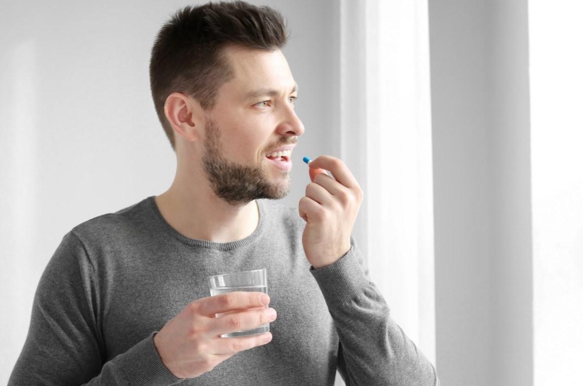Мужчина пьет капсулу эровин